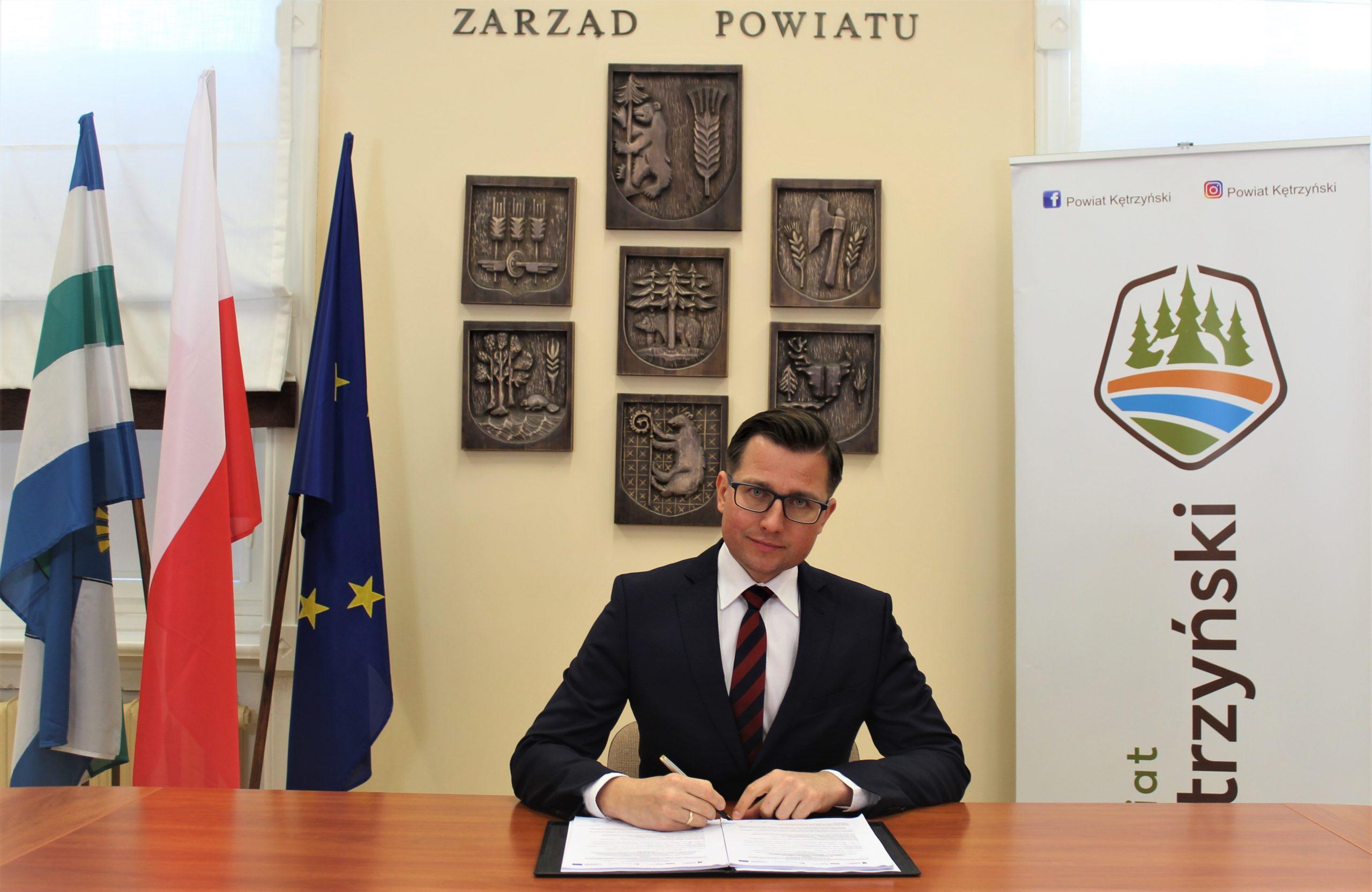 Zdjęcie przedstawia starostę kętrzyńskiego Michała Kochanowskiego podpisującego umowę o dofinansowanie