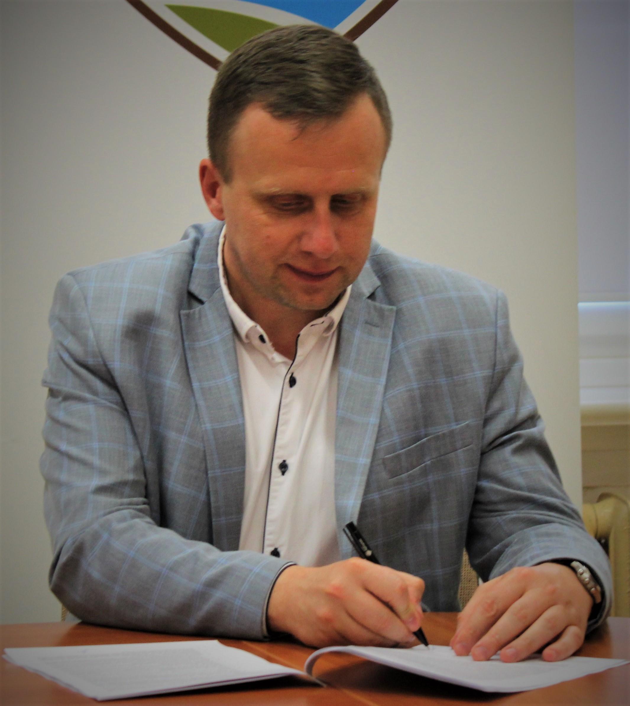 Zdjęcie przedstawia wicestarostę Andrzeja Lewandowskiego podpisującego umowę o dofinansowanie