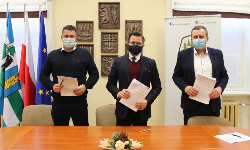 Na zdjęciu od lewej: Karol Siłkowski - wykonawca, starosta kętrzyński - Michał Kochanowski oraz wicestarosta - Andrzej Lewandowski wraz z podpisanymi umowami na realizacje projektu